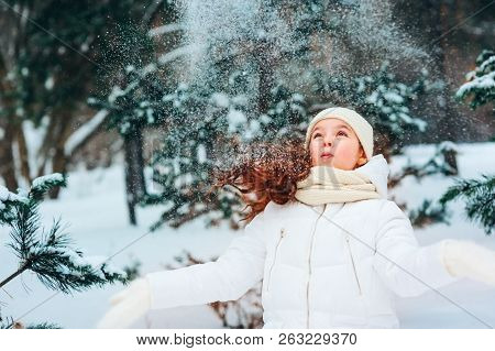 Winter Portrait Of Happy Child Girl In White Coat, Hat And Mittens Playing Outdoor In Snowy Winter F