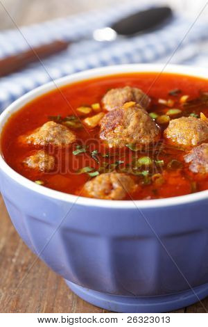 Tomato soup with meatballs in the blue bowl