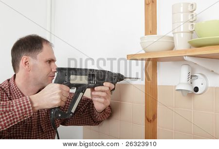 Man with power drill drilling the hole in a kitchen wall