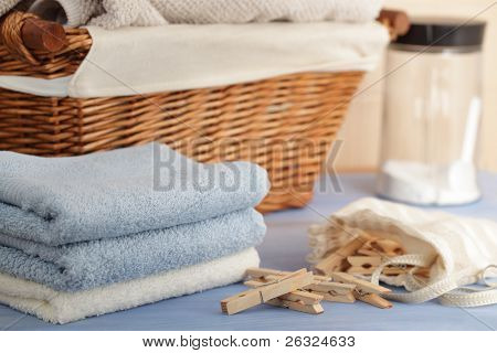 Prendedores de roupa no saco, toalhas, sabão em pó e uma cesta