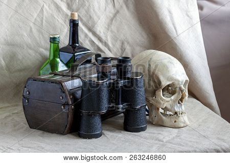 Still life with a chest, binoculars, bottles and a skull. Concept: piracy, adventure, navigation and treasure hunting. poster