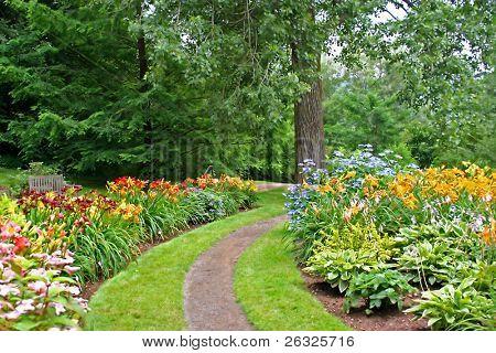 ein Pfad in einem Park durchquert Betten der Blumen, in erster Linie Daylilies.
