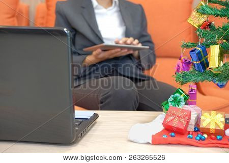 Man Sitting On Sofa Using Tablet. Businesswoman Texting Message On Touchpad During Xmas. Christmas H