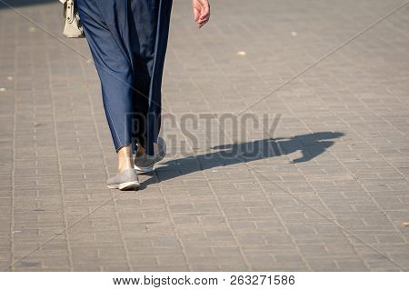 On A Sunny Day, A Woman Walk Along The Sidewalk. The Human Shadows Are Visible On The Sidewalk. View