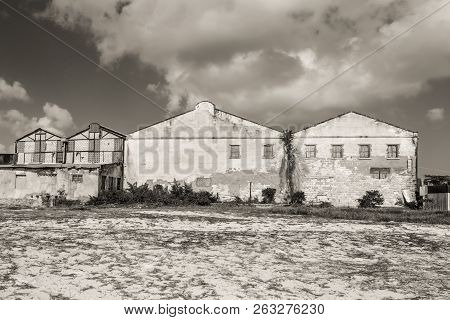 Abandoned Old Factory Buildings On The Shore. Sepia Tinted. Symbol For Economic Depressions.