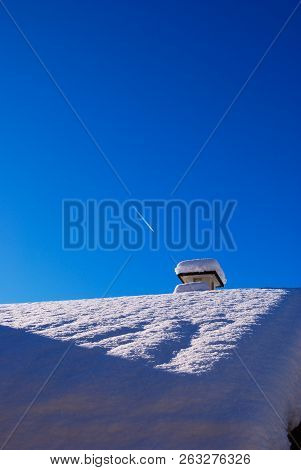 Roof With Fireplace Covered From High Layer Of Snow In Contrast With Blue Sky