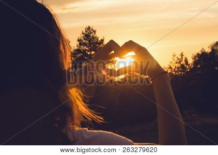 Woman Makes Heart With Hands In Sunset. Healthy People  Lifestyle. Woman Makes Heart With Hands. Nat