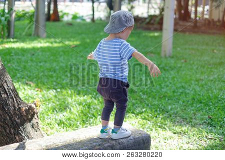 Cute Little Asian 18 Months / 1 Year Old Toddler Baby Boy Child Walking On Balance Beam In The Park