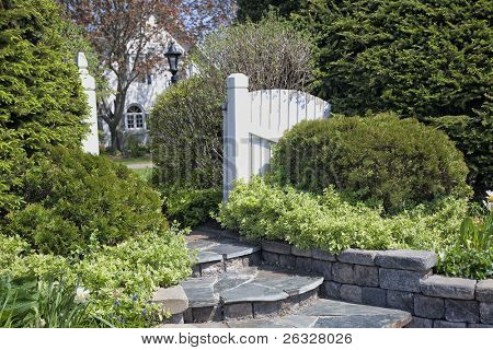 A wooden gate opened to lead to a peaceful glade. Shrubs such as euonymus, cedar and yew form an evergreen garden.