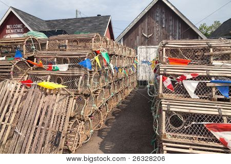 Lobster traps and commercial fisherman bait sheds some with a tuna tail on them, on a wharf on Prince Edward Island, Canada.