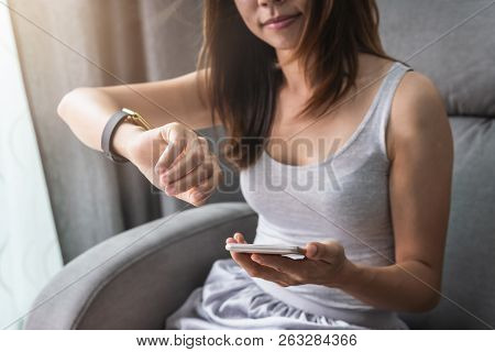 Young Asian Woman Using Smart Watch And Smart Phone At Home