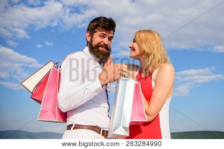 Couple With Shopping Bags Cuddle Blue Sky Background. Man With Beard Shows Thumb Up Gesture. Advice