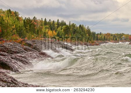 Wild Stormy Waves On Rocky Shore Of Lake Superior Along Autumn Forest