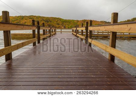 Dramatic Closeup View From The End Of A Dock On A Lake With Colorful Autumn Landscape In Background