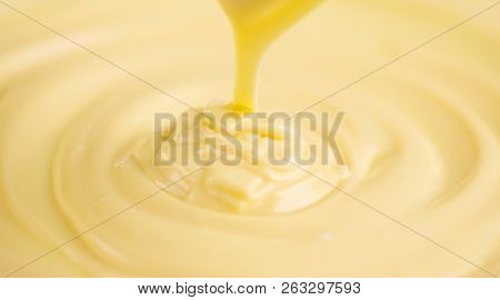 White Chocolate. Pouring melted liquid premium milk white chocolate. Close up of molten liquid hot chocolate swirl. Confectionery. Confectioner prepares dessert, icing poster