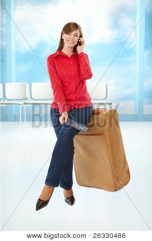 Chica de turista sentada en una maleta con un billete en su mano y el teléfono móvil
