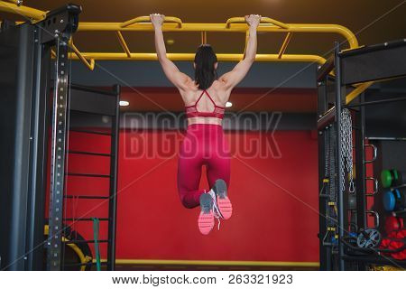 Back View Of Muscular Adult Sportswoman Hanging On Metal Bar In Gym Doing Chin-ups