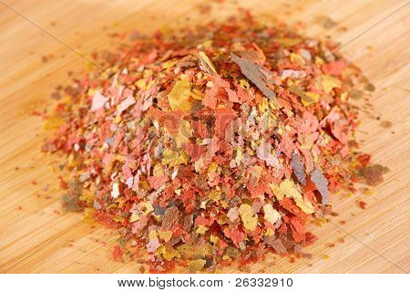 Heap of dry complete multi-ingredient flake food for daily feeding of all ornamental fish