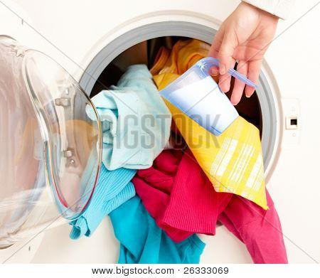Close-up on female hand adding washing powder to washing machine full of coloful clothes