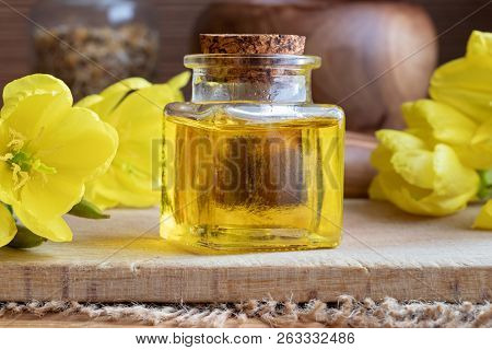 A Bottle Of Evening Primrose Oil With Fresh Flowers
