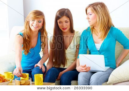 Three happy friends beautiful girls sitting on sofa in home with cups, chips, cookies and laptop