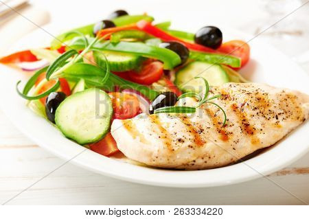 Grilled chicken breast with green and red pepper, cherry tomatoes, lettuce, black olives, cucumber, pink pepper and fresh rosemary. Home made food. Concept for a tasty and healthy meal. Close up.
