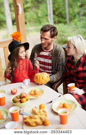 Family of young parents and their adorable daughter sitting by halloween table and discussing symbols of holiday