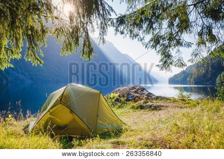 Sunlit camping tent at scenic campsite on a lake shore with mountain range in background - wild camping in Norway poster