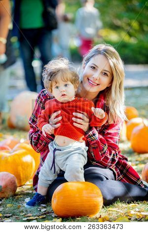 Young Mother With A Child On A Lawm With A Pumpkins. Autumn Season Time.