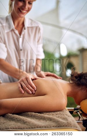 Close up of smiling massage therapist doing a back massage on outdoor