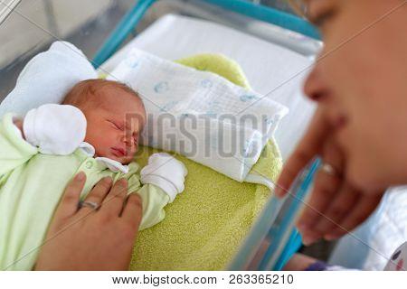 Loving mother and newborn baby boy sad cryingin hospital