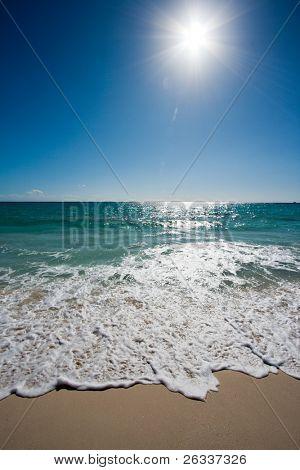 Beautiful beach, sun and waves of Caribbean Sea