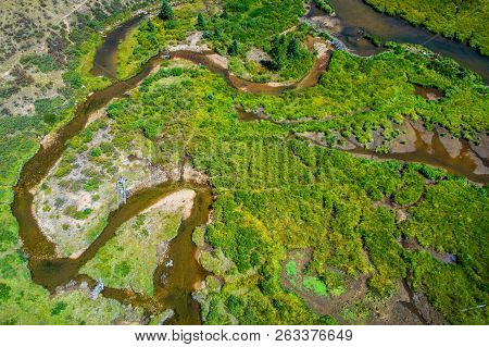Aerial Drone View Looking Down On Lush Green Valley Floor With Windy Rivers And Amazing Meandering S