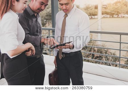 Group Of Business Asian People Standing And Talking About Summary Report On Tablet Screen.