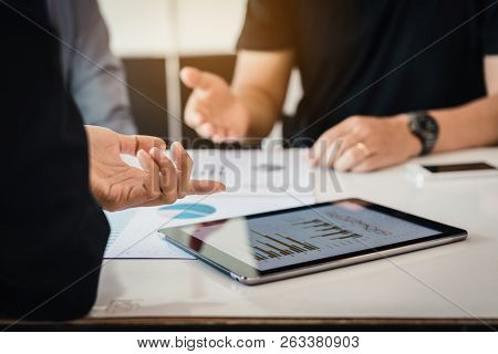 Manager And Employee Analyzing Finance Cost With Tablet At Business Meeting With Discussion Working