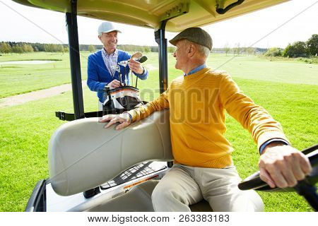 Senior man sitting in golf car while talking to his buddy preparing golf clubs behind