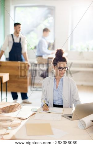 Young female analyst sitting in front of laptop and solving organization moments in working environment