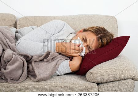 Sick Woman Lying On The Sofa Blowing Her Nose - Sinus Infection