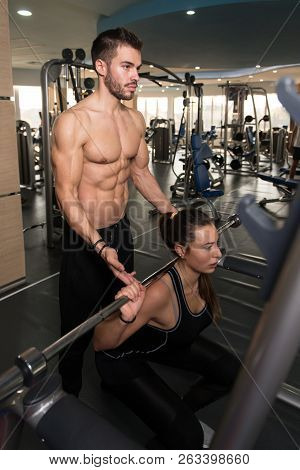 Woman With Personal Trainer At Barbell Squat