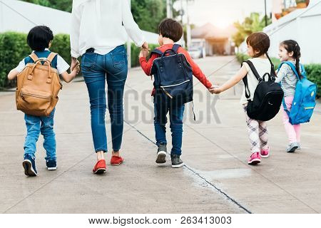 Back To School Students Mother Group Going School Together. Parent Send Little Boy And Girl For Firs