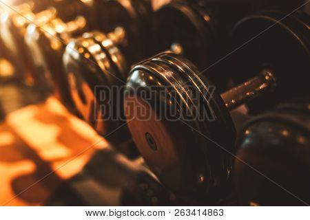 Black Steel Dumbbell Set. Close Up Of Dumbbells On Rack In Sport Fitness Center Background. Workout