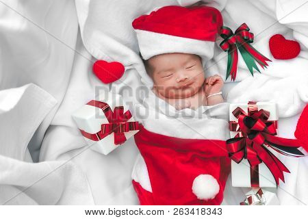 Sleeping Newborn Baby Face In Christmas Hat With Gift Box From Santa Claus And Yarn Heart On White S