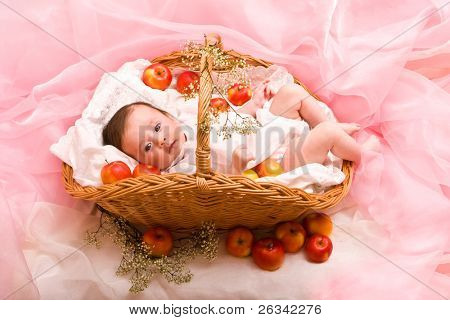 Cute baby girl in the basket with apples