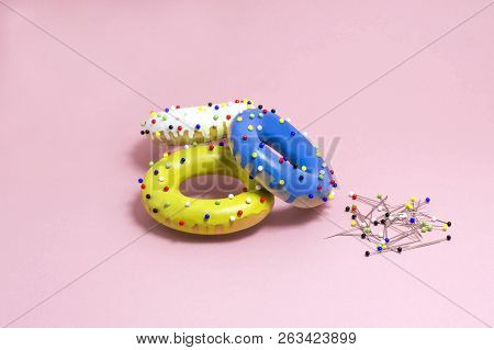 Humorous Imitation Of Donuts From Painted Bagels With Multi-colored Pins. Artificial Object That Mim