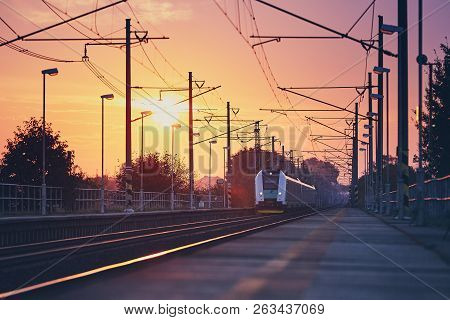 Passenger Train Commuting To Railroad Station At Colorful Sunrise.