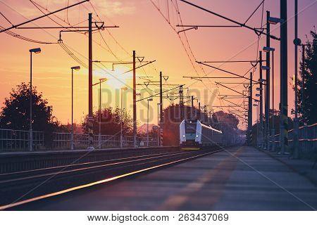Passenger Train Commuting To Railroad Station At Colorful Sunrise.
