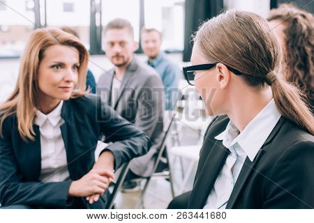 Selective Focus Of Attractive Businesswomen Sitting On Chairs And Talking In Conference Hall