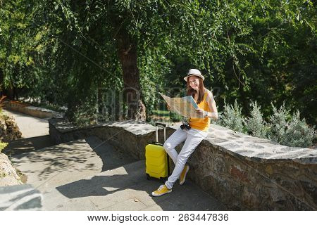Smiling Traveler Tourist Woman In Yellow Clothes, Hat With Suitcase Holding City Map Sitting On Ston