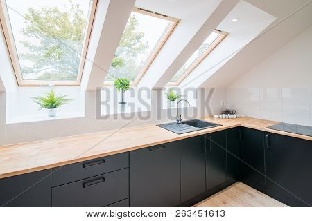 Bright Kitchen With Slanted Ceiling. Modern Bright Flat Apartment In The Attic. Kitchen With Black K