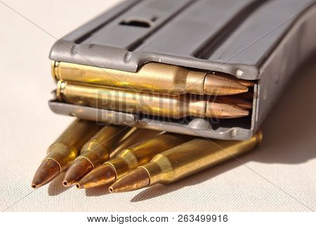 A metal rifle magazine loaded with .223 caliber bullets laying on top of four bullets of the same caliber poster